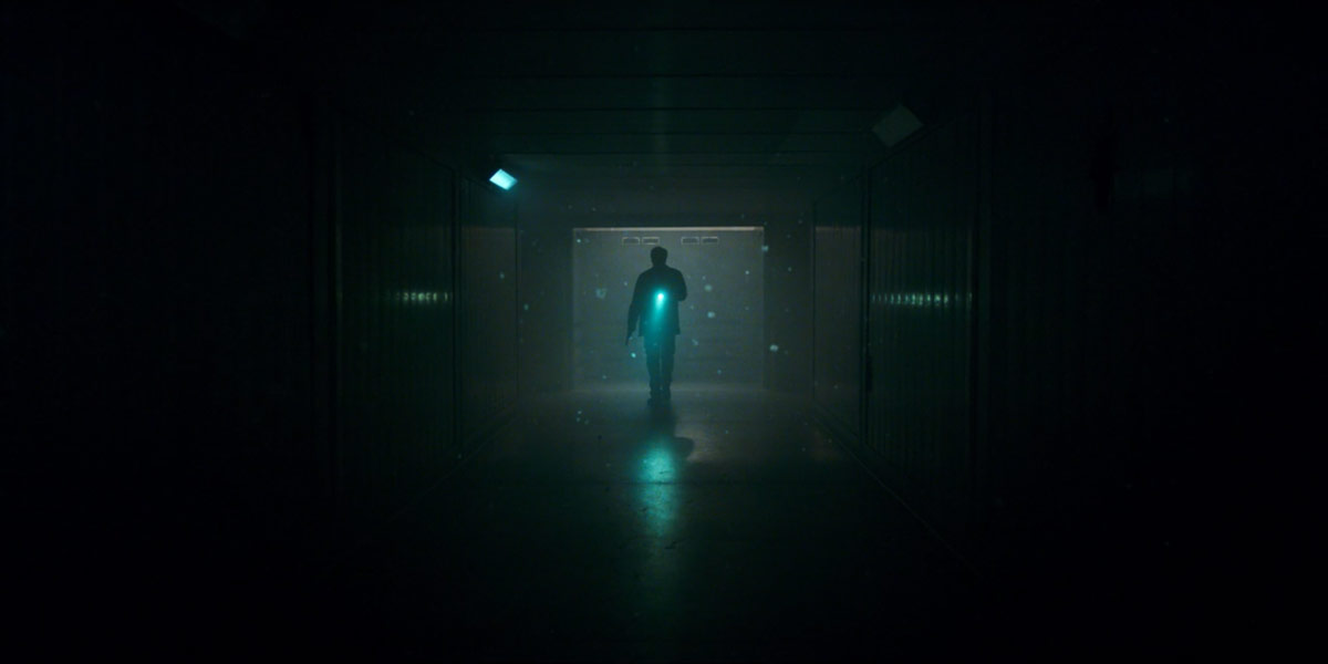 SURPRISE IN THE ELEVATOR: At the beginning of the first episode, viewers are greeted with a mortified scientist bolting through a dim, metallic corridor throughout an unnamed facility. Unfortunately his attempts to escape were quickly rendered futile, as a surprise was awaiting his arrival in the elevator.