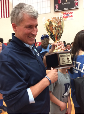 Headmaster Seivold proudly holds the Headmaster's Cup.