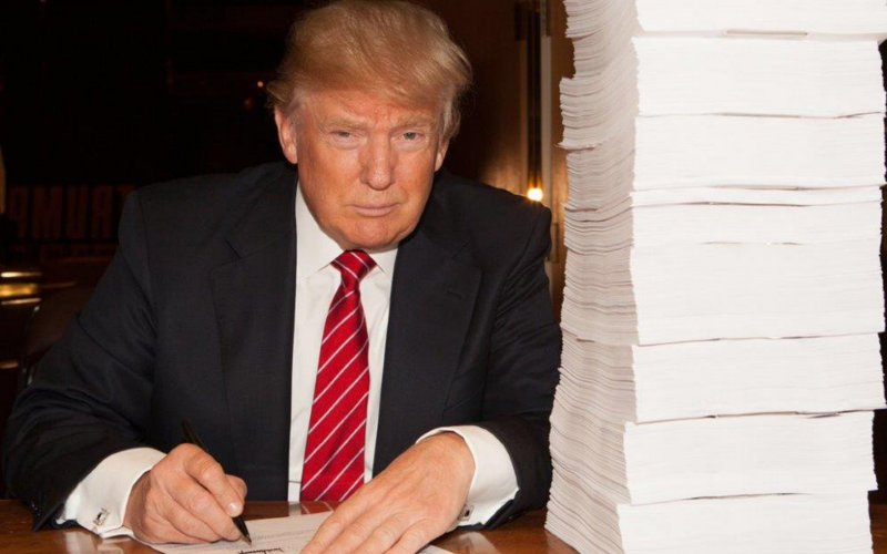 Trump poses next to a stack of tax returns. Source: The Daily Beast