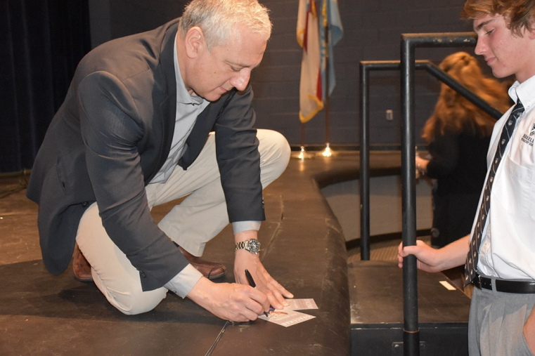 SIGN+HERE+PLEASE%3A+Before+the+presentation%2C+students+line+up+to+get+Massimino%E2%80%99s+signature.+Many+students+were+impressed+by+Massimino+and+his+engineering+accomplishments+on+the+Hubble+Space+Telescope.+