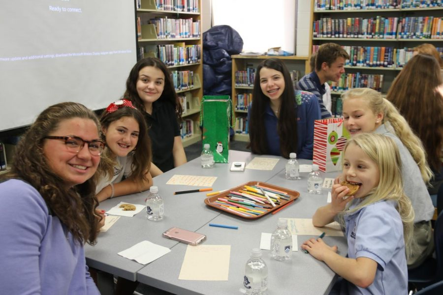 HAPPY TO HELP: Gabriella Donahue '20 (left) and Sophia Monticciolo '20 (center) pause for a photo with new friends from Middle and Lower Division, as one very excited Lower Division student enjoys a snack.