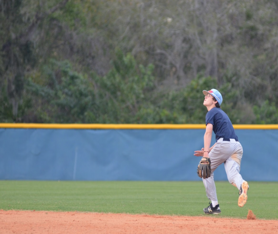 OUTSTANDING OUTFIELDER: Andrew Dimisa '21 looks up as he runs towards the baseball while still in mid-air.