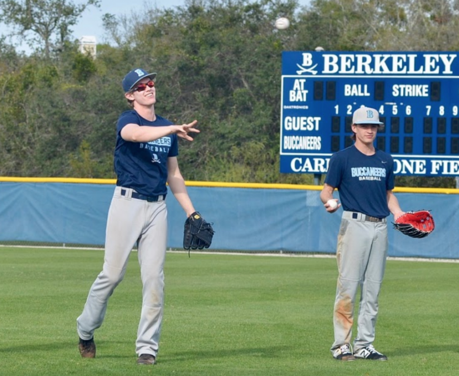 WARMING UP: (from left) John Dooley '19 and Alex Haire '20 warm up their throwing arms at the start of practice.