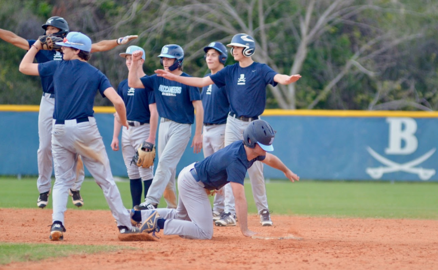 SAFE: Gunnet Carlsen '22 slides into second base during a drill as his teammates eagerly cheer him on.
