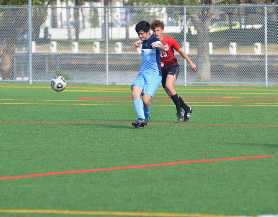 FANCY FOOTWORK: Turning on his heel Dominick Lee '20 redirects himself in front of the ball, blocking his opponent's opportunity to pass to a teammate. Photo by Sloane Daley